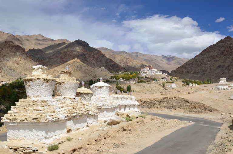 Buddhist Chortens in the foreground and Likir Monastery in the background, situated in a typical Ladakh landscape, near Leh, Ind