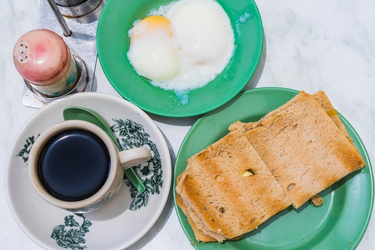Singapore Breakfast called Kaya Toast, Coffee bread and Half-boiled eggs, Chinese coffee in vintage mug and bread toast with a local jam made from egg