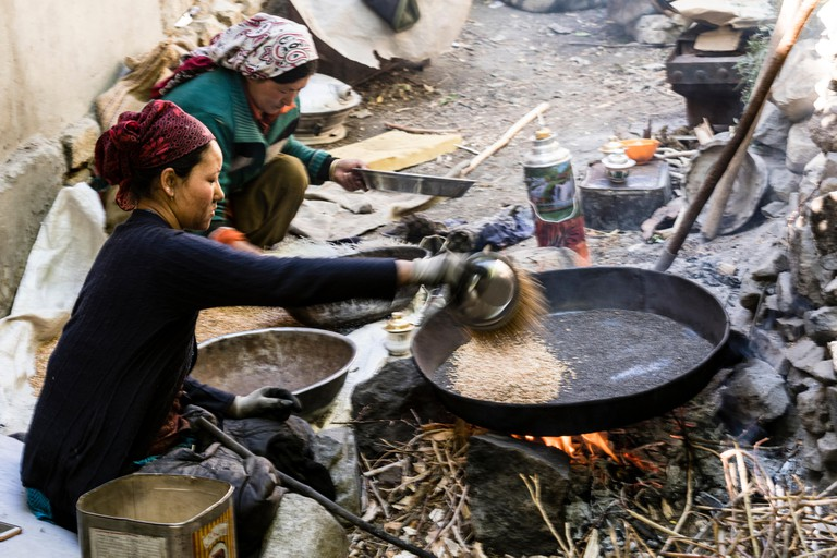 A woman roasting barley to make  a traditional Ladakhi food called Tsampa in a village in Ladakh, India