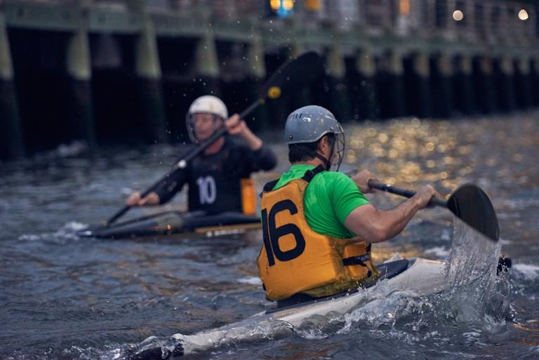 Players maneuver around the playing area via kayaks