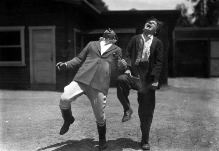 Photograph of Charlie Chaplin and Douglas Fairbanks laughing.