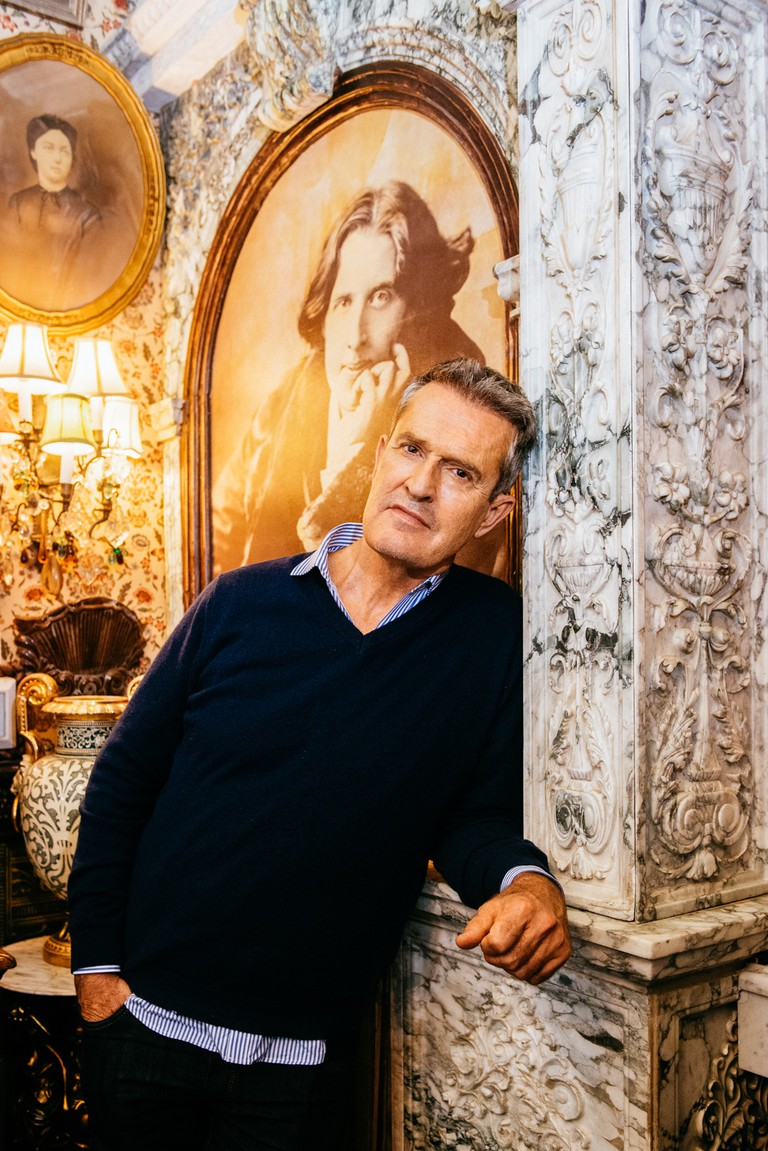 Rupert Everett with a portrait of Wilde at Oscar Wilde NYC