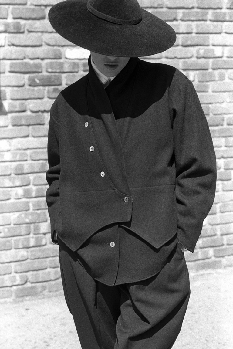 Model wearing a split-level jacket and matching black wool contoured and cropped pants from the Yohji Yamamoto fall 1981 ready to wear collection.