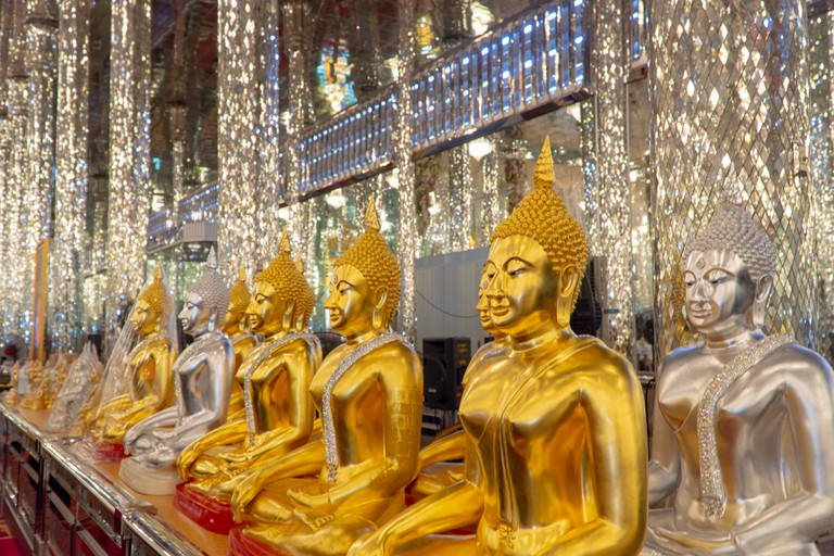 Wat tha sung, Uthai Thani / Thailand: Selective focus of Buddha statues in gold and silver color with the wall tiles made from mirrored glasses.