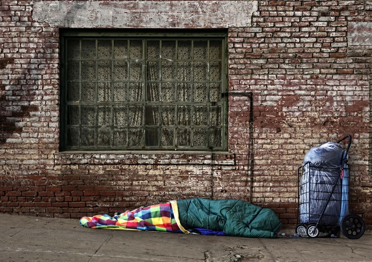 A homeless person photographed sleeping outdoors. People who are homeless are most often unable to acquire and maintain regular, safe, secure and adequate housing.