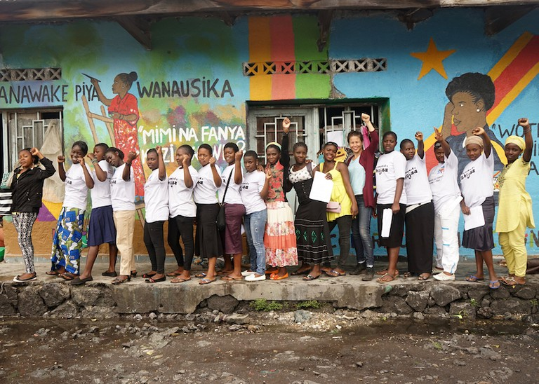 "The participants and project staff in front of the ""Women in the workforce"" mural, April 2016."