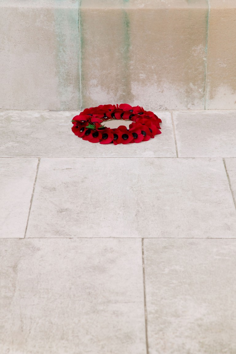 A single poppy wreath at the base of a war memorial on rememberance Sunday