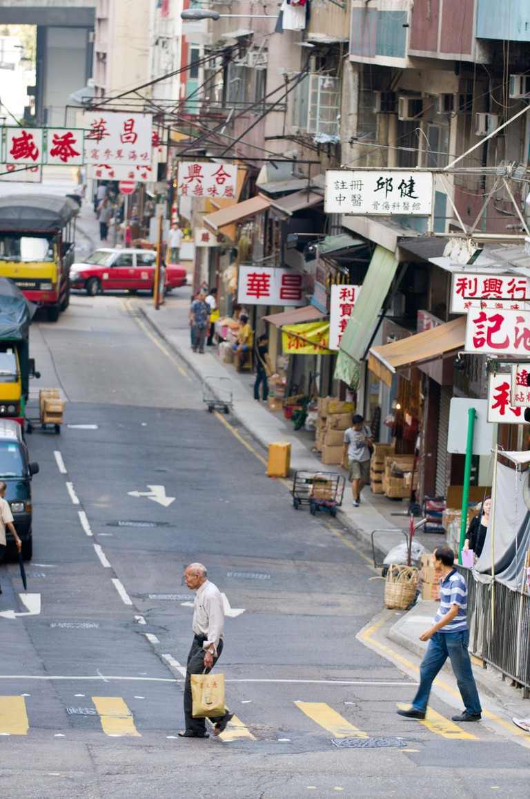 Man crossing Hong Kong street in Sheung Wan