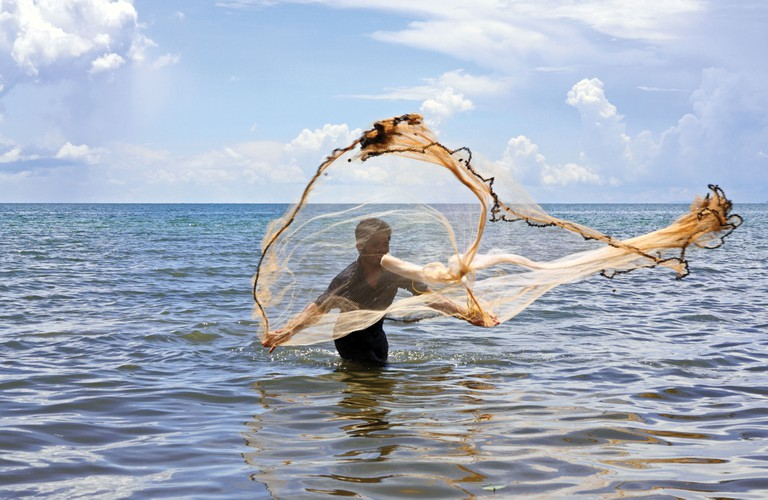 Fisherman fishing casting his net in Kep beach, South Cambodia