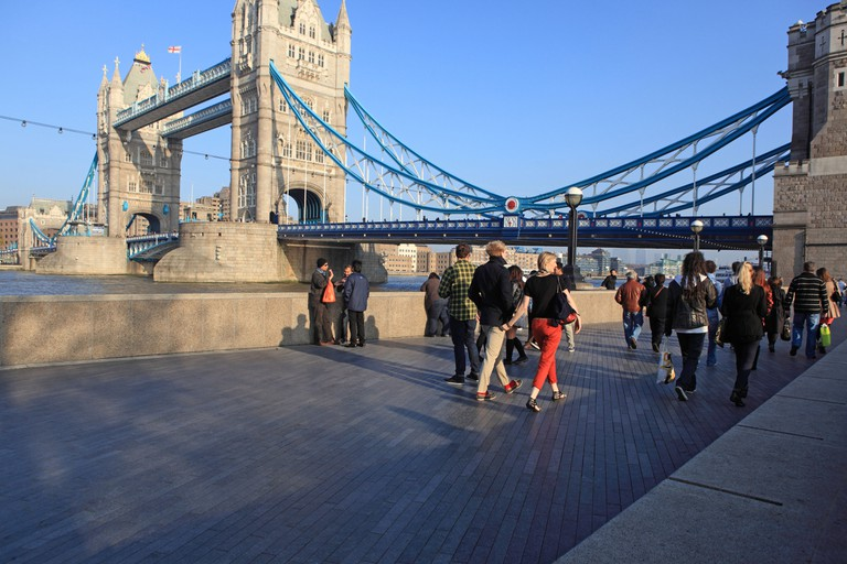 People walking along Queen's Walk next to the River Thames, London.