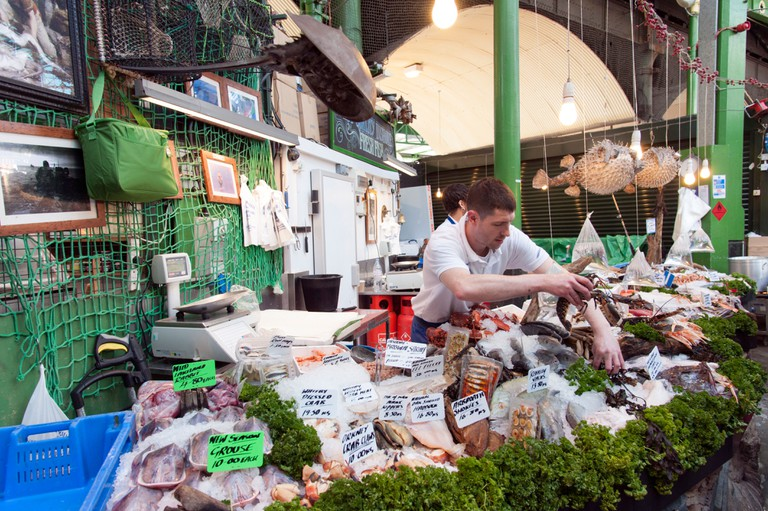 A fishmonger at Borough Market, London, sets up his offerings