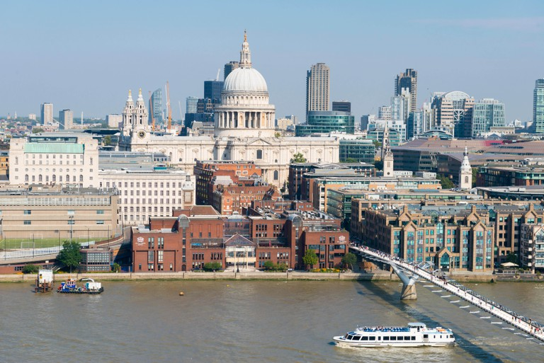 Tourist boat cruise crossing Milenium Bridge & St Pauls Cathedral