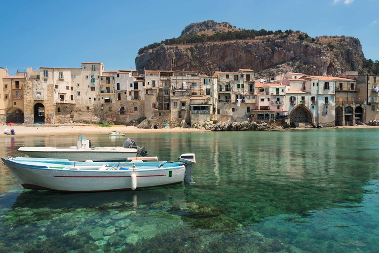 Two dinghy boats in the emerald green water of the small port at the city beach in the old town of Cefalu near Palermo in Sicily, Italy.