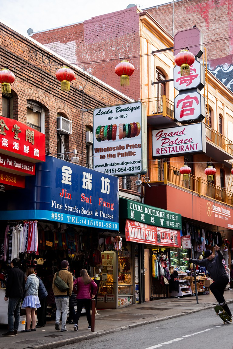 Tourists browse a Chinatown store for a memento while enjoying a time-honored neighborhood tradition: window shopping