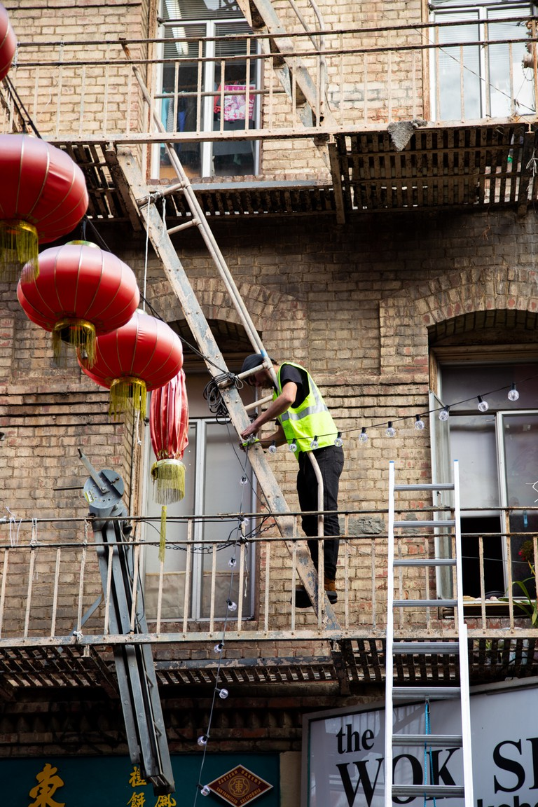 A worker performs maintenance on a few of the thousands of red lanterns suspended over Grant Avenue
