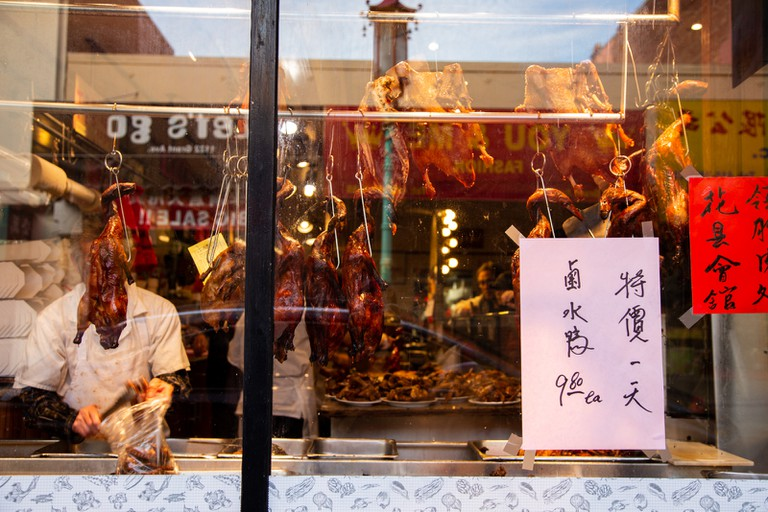 Peking duck hangs in windows, plated and ready to serve on the counter within