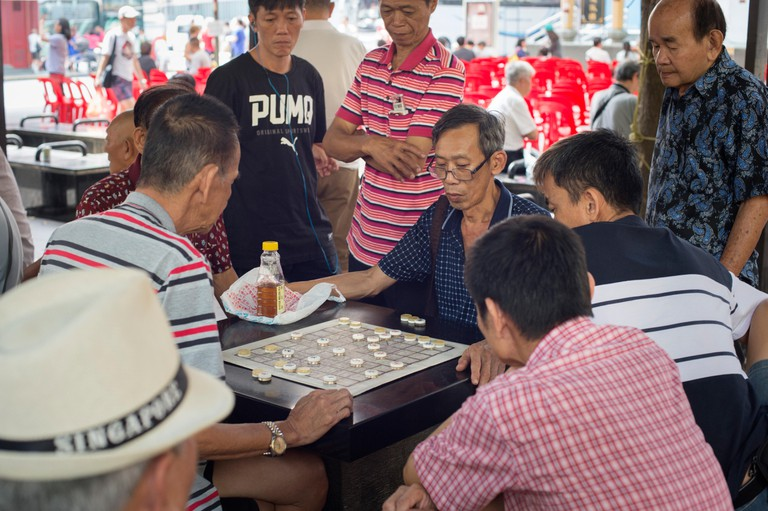 Men play checkers on a street of Chinatown district in Singapore.