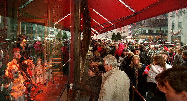 Tourists and pedestrians crowd the sidewalks in front of New York's Saks Fifth Avenue