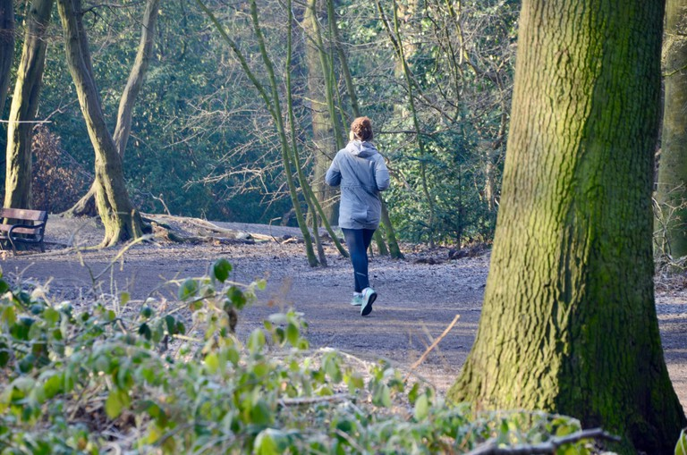 Woman jogging on a path in Highgate woods, North London.