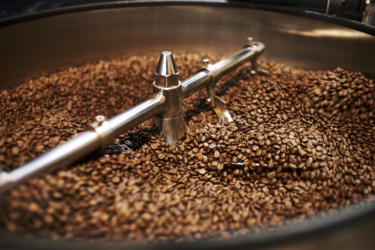 Freshly roasted coffee beans being mixed.