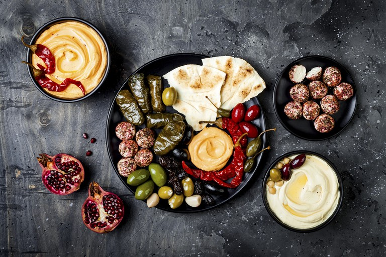 Middle Eastern meze choices with pita, olives, hummus, stuffed dolma, labneh cheese balls in spices.