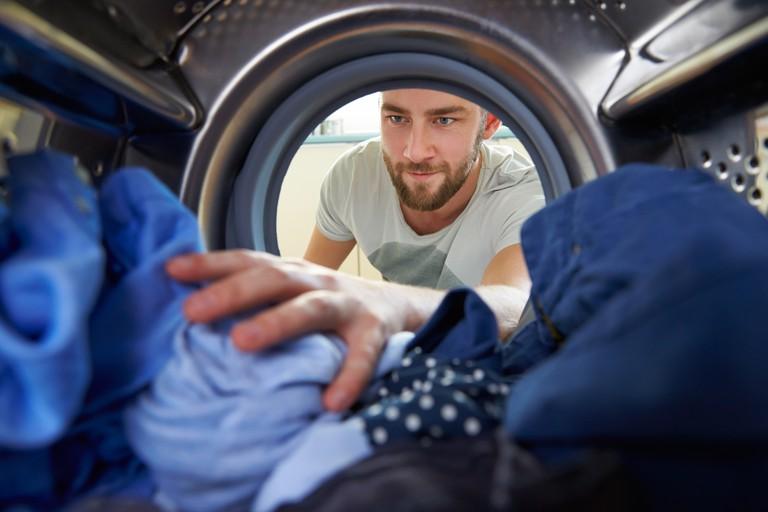 Man doing laundry reaching inside washing machine.