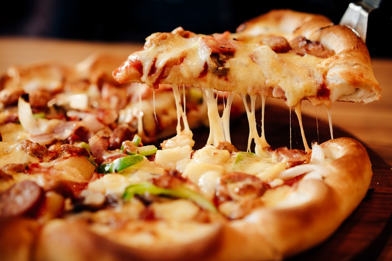 Slice of hot pizza with meat topping, sauce, bell pepper and vegetables.