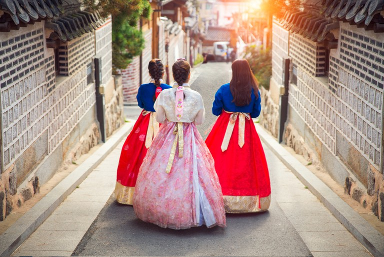 Women in Hanbok, the traditional Korean dresses, walking in an ancient part of Seoul, South Korea.