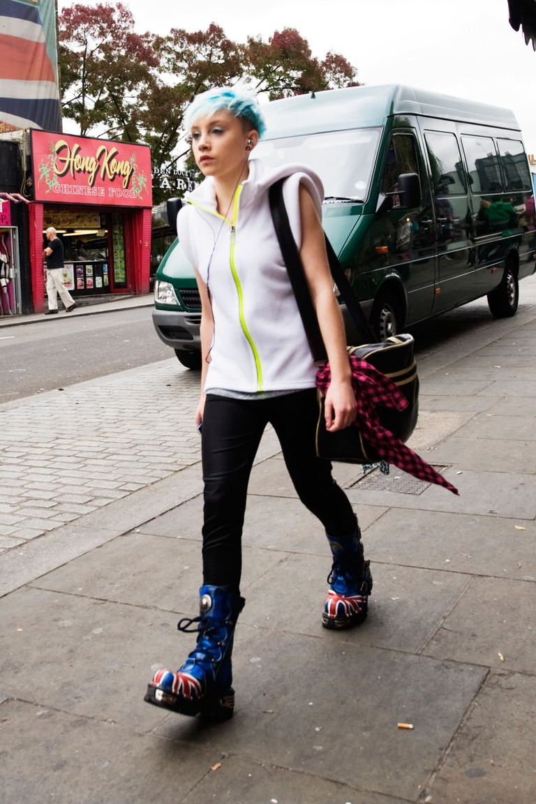 London Camden Town Lock Stables market pretty young punk girl walking with blue hair blue Dr Martens boots with Union Jack large bag red black check