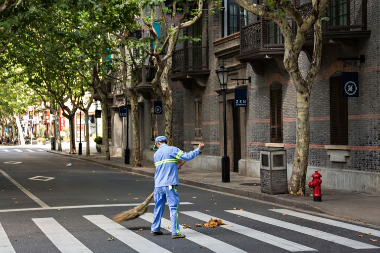 A street sweeper cleans up in Xintiandi Plaza shopping district Shanghai, China