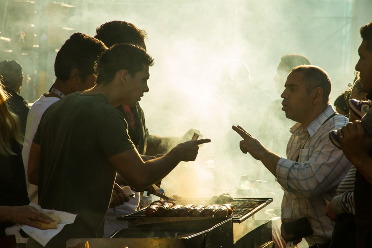 A customer ordering food from a street vendor in Buenos Aires.. Image shot 2013. Exact date unknown.
