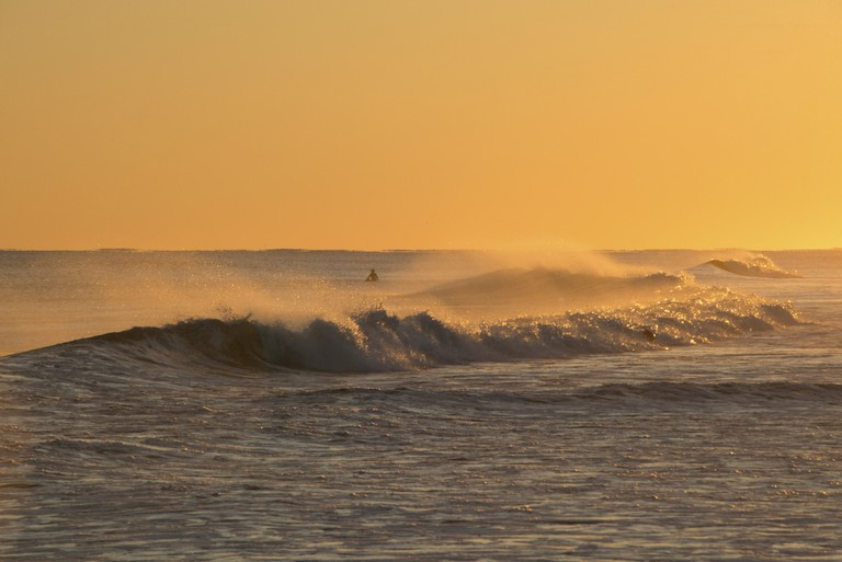 A surfer in the ocean at sunset in the Rockaways, Queens, New York City.