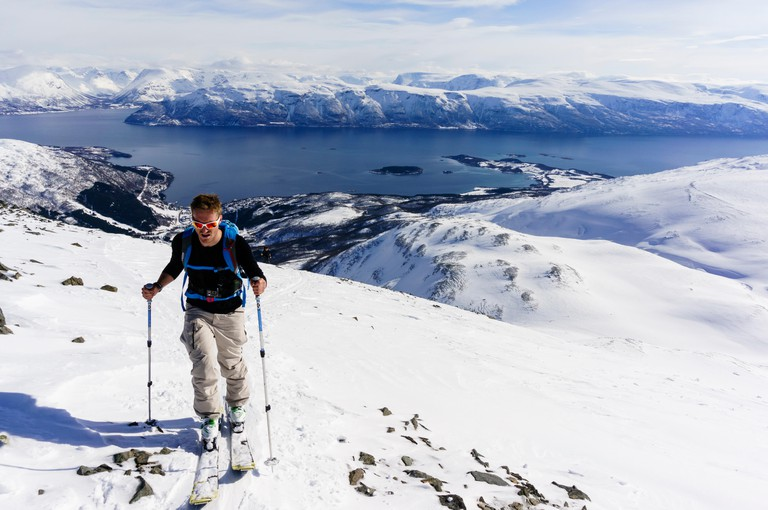 Skier ski touring on the way up Rornefjellet above Lyngenfjord, Lyngen Alps, Troms, Norway.