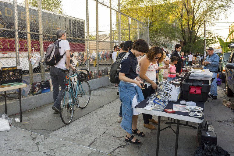 Young People visiting Bushwick Section of Brooklyn Weekend Flea Market on street.