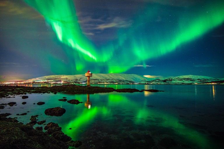 Northern lights dancing over fjord, Tromso, Northern Norway.