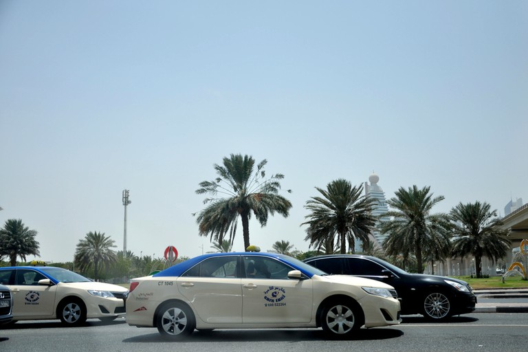 Dubai City Taxis in traffic with palms