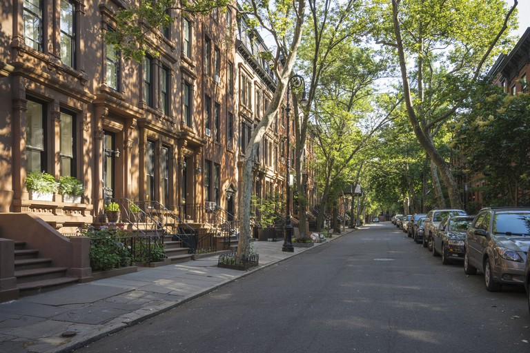 Tree-lined street with attractive brownstone buildings in affluent residential neighborhood in Brooklyn Heights, New York.