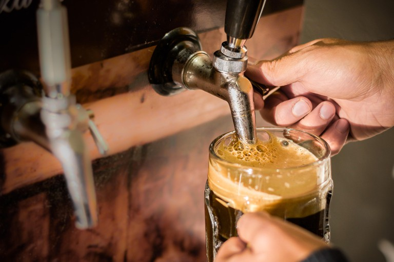 Bartender filling up with craft beer a pint glass