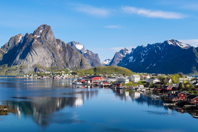 Reflections of mountains in scenic natural fishing harbour in summer. Reine, Moskenes, Moskenesoya Island, Lofoten Islands, Nordland, Norway