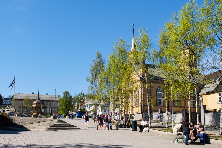 Street scene with people in pedestrianised square with Catholic church Den katolske Kirke in summer. Erling Bangsunds plass, Tromso, Troms, Norway