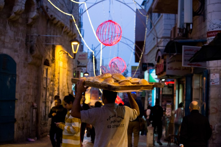 Man carries fresh pita bread as Bethlehem, Palestine, lights up for the Christmas holidays.