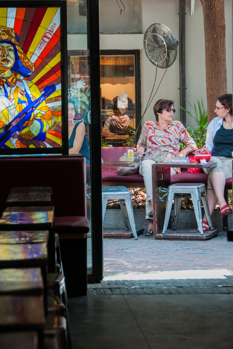 Foreigners relax in the spring sun outside the Kommune cafe in the lanes of Tianzifang, Shanghai. Seen from inside with a propaganda image of a Chines