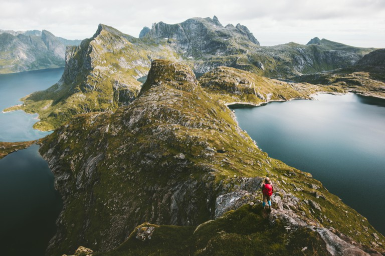 Traveler alone with backpack hiking on mountain ridge landscape hiking Traveling lifestyle adventure concept active vacations in Norway outdoor aerial