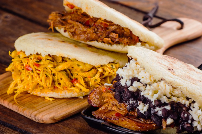 Venezuelan traditional Arepas freshly made, with 3 different fillings to taste chicken, roasted meat and pabellon on a wooden background