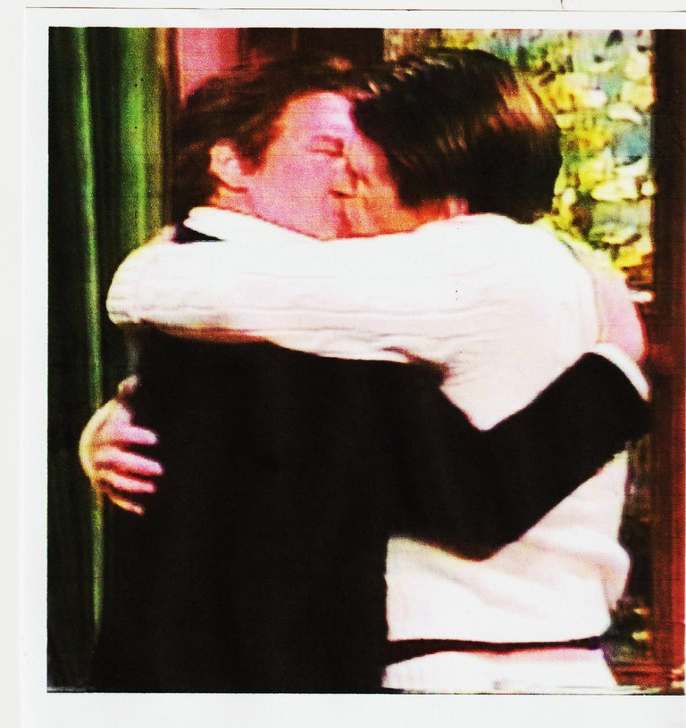 Alec Baldwin (right) and Phil Hartman kissing each other in a Saturday Night Live skit.