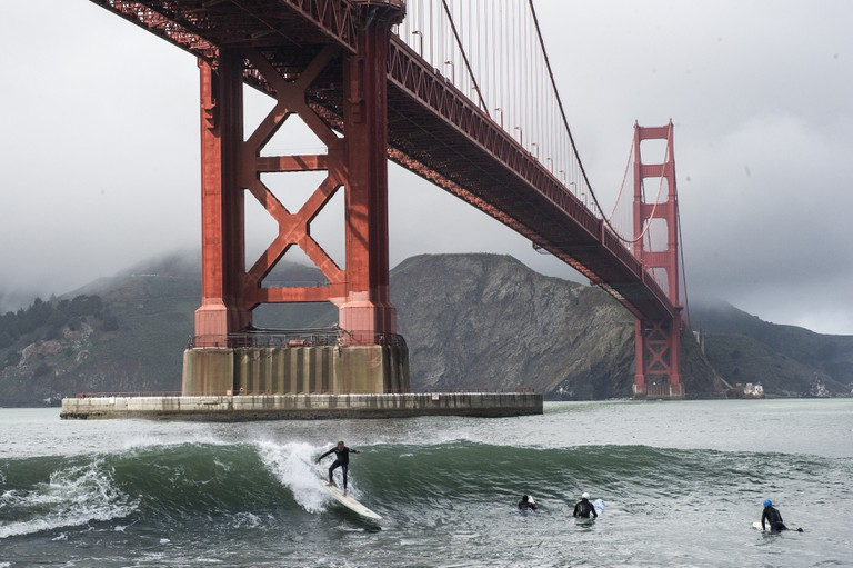 Surfers catch waves under the Golden Gate Bridge in San Francisco, America.