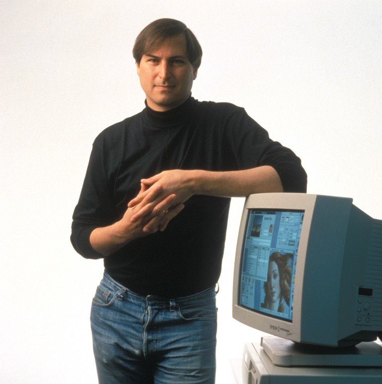 Steve Jobs, at age 39, CEO and co-founder of Apple Computer Corporation, leaning on a monitor, which is on top of his newest product : the Apple Power Macintosh 6100, a revolutionary workstation-class personal computer line, replacing Apple's Quadra.