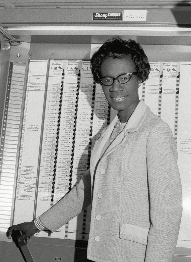Shirley Chisholm poses at voting booth in Bethany Methodist Church in Brooklyn, New York.