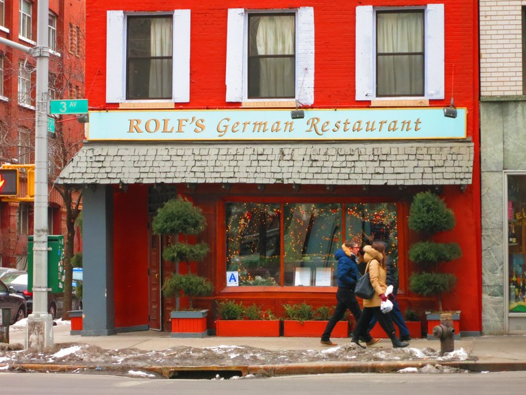 A group of friends passing Rolf's German Restaurant on 3rd Avenue in Manhattan.