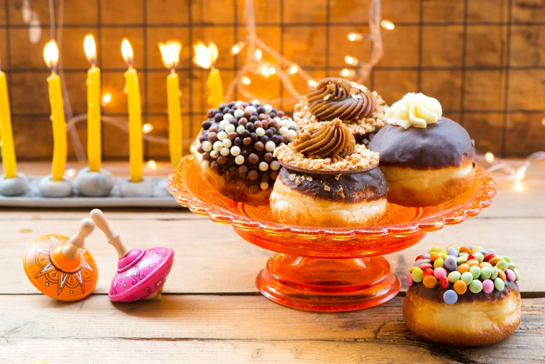 Traditional Hanukkah donut, dreidels and hanukiah.
